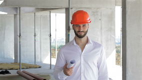 Builder walking with set of plans under his arm. Young caucasian builder walking with set of plans under his arm at the building under construction. Bearded stock video footage