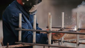 Builder weld the pipe to the construction. From weld flew the sparks in different sides stock footage
