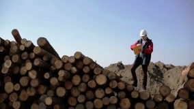 A builder in a white helmet and red jacket is standing on the pile of logs. Worker is waiting somebody and calling him waving hand. Man holding folder with stock video