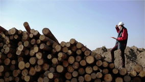 A builder in a white helmet and red jacket is standing on the pile of logs. Worker is watching around and making notes in a document stock footage