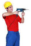 Builder wielding a power drill. Young person wielding a power drill Stock Photo