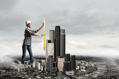 Builder woman taking measures . Mixed media Royalty Free Stock Images