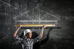 Builder woman taking measures . Mixed media Stock Image