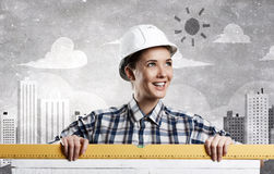Builder woman taking measures . Mixed media Stock Photography