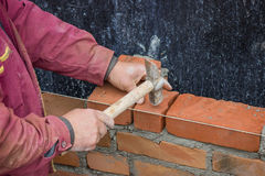 Builder worker with bricklayer hammer laying solid clay brick Stock Photos