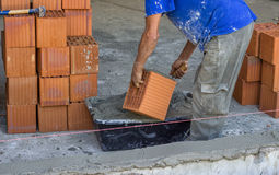 Builder worker butter the ends of each new block Stock Photography