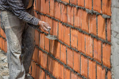 Builder worker, clay block wall and trowel. Builder worker using the sharp end of the trowel, scrape off any excess mortar that spreads beyond the joint Royalty Free Stock Image