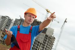 Builder worker with clipboard. Engineer builder at construction site directing up with finger Royalty Free Stock Photos