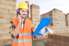 Builder worker with clipboard talking on cellphone. In front of building under construction as successful job concept Royalty Free Stock Photos