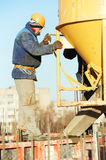 Builder worker at concrete pouring into form Stock Photo