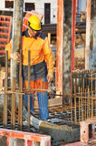 Builder worker at concrete pouring work Stock Photos