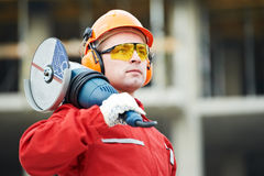 Builder worker at construction site. Builder worker in safety protective equipmant with grinding machine power tool at construction site Stock Photos