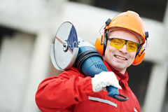 Builder worker at construction site. Builder worker in safety protective equipmant with grinding machine power tool at construction site Royalty Free Stock Photo