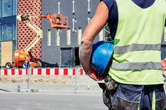 Builder worker on construction site. Building and workforce. Constructor worker with helmet in hands standing over construction site Royalty Free Stock Photos