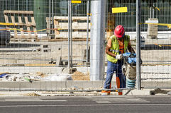Builder worker at construction site makes sidewalk near new office building. Vilnius, Lithuania - June 29, 2016. Stock Image