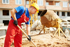Builder worker at construction site with shovel. Builder man working with shovel during concrete cemant solution mortar preparation at construction site Stock Photography
