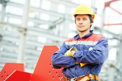 Builder worker at construction site. Builder worker in uniform and safety protective equipment at construction site in front of metal construction frames Stock Image
