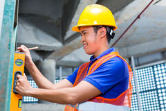 Builder or worker controlling wall on construction site Royalty Free Stock Photography