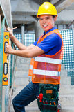 Builder or worker controlling wall on construction site. Asian Indonesian builder or craftsman with hardhat and bubble level controlling or checking a wall of a Stock Photos