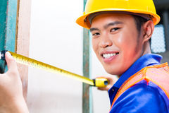 Builder or worker controlling wall on construction site Royalty Free Stock Photos