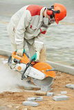 Builder worker cutting curb with disc saw. Construction worker at curb stone cutting work by cut-off disc saw with diamond wheel Stock Photography