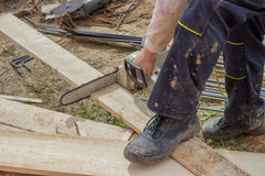 Builder worker cutting wooden plank with chainsaw Royalty Free Stock Photo