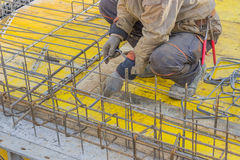 Builder worker gearing up steel rods for a concrete 2. Builder worker gearing up steel rods for a concrete slab pour. Installing Steel Work Before Concrete Pour Royalty Free Stock Images