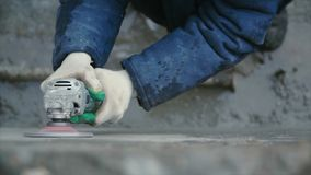 Builder worker with grinder machine cutting finishing concrete wall at construction site. Clip. Worker grinds concrete. Wall Stock Photography