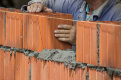 Builder worker installing clay block wall, lay clay block Stock Photography