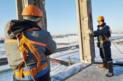 Builder worker installing concrete panel. Builder worker in safety protective equipment installing concrete wall panel at building construction site Stock Image