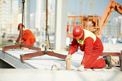 Builder worker installing concrete slab. Builder worker in safety protective equipment installing concrete floor slab panel at building construction site Royalty Free Stock Photo