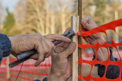 Builder worker Installing Construction Safety Fence 2 Stock Photos