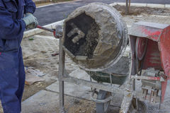 Builder Worker Mixing Cement. At construction site Stock Photo