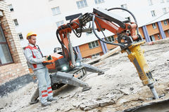 Builder worker operating demolition machine. Builder worker in safety protective equipment operating construction demolition machine robot Royalty Free Stock Photography