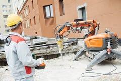 Builder worker operating demolition machine Stock Photo
