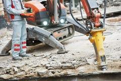 Builder worker operating demolition machine. Builder worker in safety protective equipment operating construction demolition machine robot Royalty Free Stock Photo