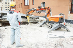 Builder worker operating demolition machine Stock Photos