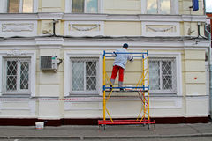 Builder worker painting facade of building with roller. Moscow, Russia - April 23, 2016: Builder worker painting facade of building with roller in Moscow Royalty Free Stock Photography