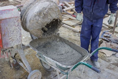 Builder worker pouring cement from cement mixer into wheelbarrow. At construction site. Rotating drum is very old and rusty Royalty Free Stock Image