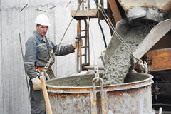 Builder worker pouring concrete into barrel Stock Photos
