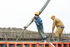 Builder worker pouring concrete into form Stock Photo