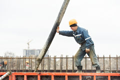 Builder worker pouring concrete into form Stock Images