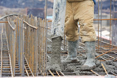 Builder worker pouring concrete into form Stock Photography