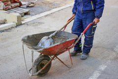 Builder worker pushing gravel wheelbarrow Stock Images