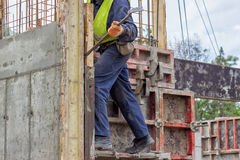 Builder worker removing formwork elements with crowbar Stock Photos