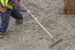 Builder worker standing in fresh cement, using a metal rake to f Stock Photography