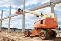 Builder worker stop up concrete pole. Builder worker putting cement mortar on concrete pole joint at construction site using lifting boom machinery Royalty Free Stock Photos