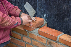 Builder worker with trowel laying solid clay brick Stock Photography