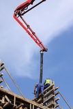 Builder worker with tube from truck mounted concrete pump Royalty Free Stock Image
