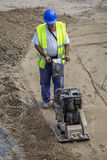 Builder worker use vibrating plate compactor Stock Photography